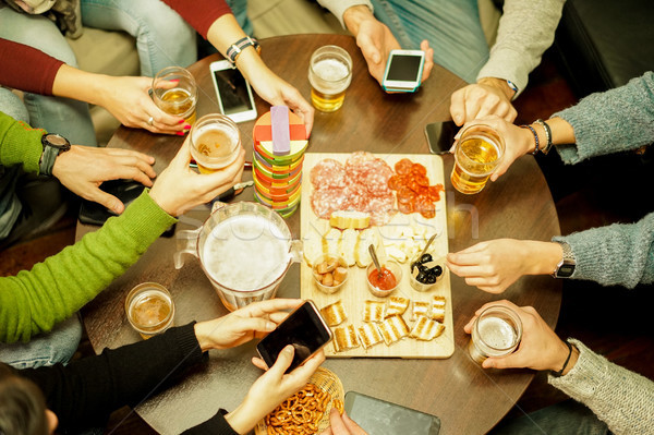 Top view of young people toasting beers and eating some snack ap Stock photo © DisobeyArt
