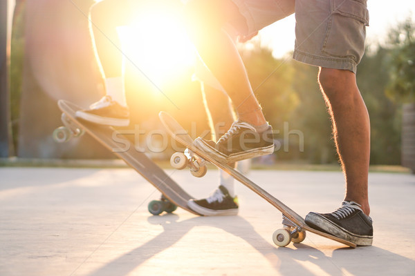 Closeup of two friends training with skateboard at sunset outdoo Stock photo © DisobeyArt