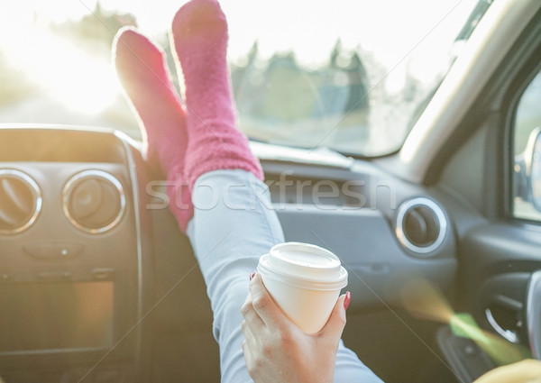 Stock photo: Young drinking coffee take away with feet in warm socks on car d