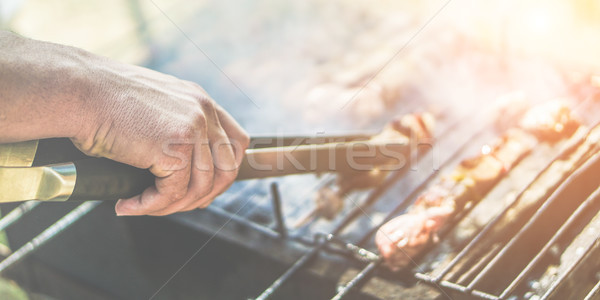 Young man cooking meat on barbecue at home in backyard - Chef pu Stock photo © DisobeyArt
