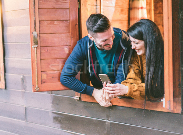 Happy couple having fun with smartphone inside camping wood hous Stock photo © DisobeyArt