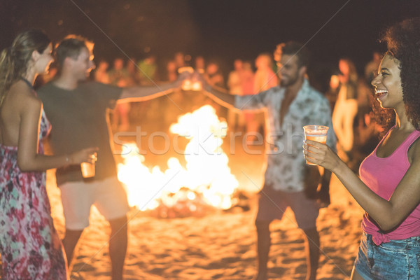 Happy friends drinking beer at beach festival with bonfire in ba Stock photo © DisobeyArt