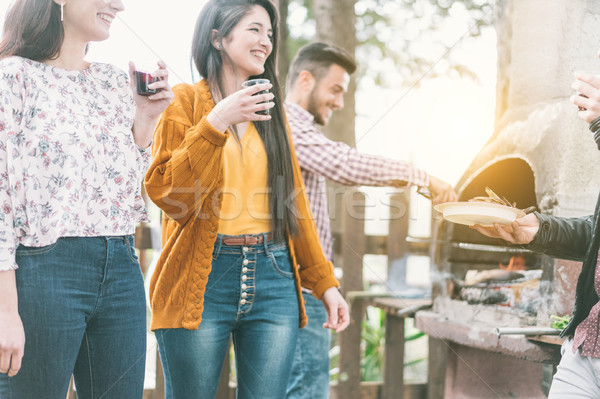 Stock photo: Happy friends cooking meat and vegetables at barbecue dinner out