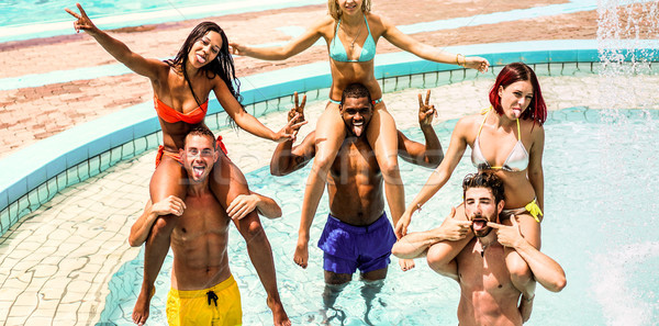 Happy friends having fun in water aqua park on summer vacation - Stock photo © DisobeyArt