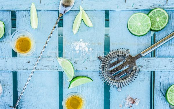 Top view of tequila shots with limes and salt on blue wood bar c Stock photo © DisobeyArt