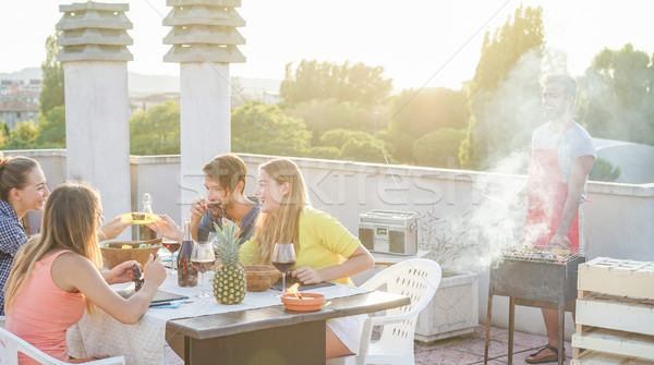 Stock photo: Happy friends eating and drinking red wine at barbecue party - Y