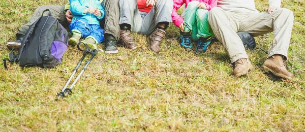 Legs and trekking equipment of traveler family sitting on a high Stock photo © DisobeyArt