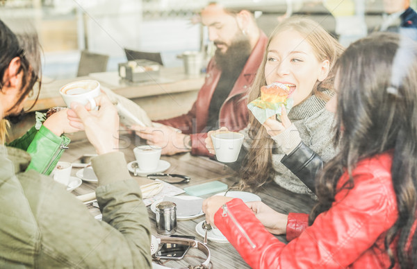 Happy friends eating breakfast and drinking coffee at bar restau Stock photo © DisobeyArt