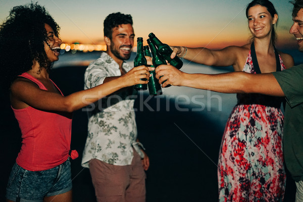 Happy friends drinking beer and having fun on the beach after su Stock photo © DisobeyArt