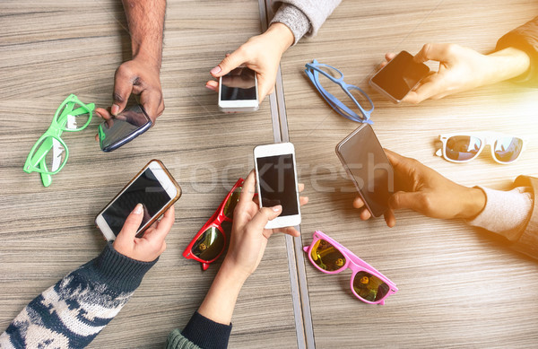 Group of multiracial people having fun together with smartphones Stock photo © DisobeyArt