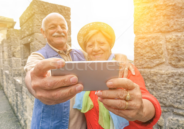 Senior couple taking a selfie at castle outdoor with back lighti Stock photo © DisobeyArt