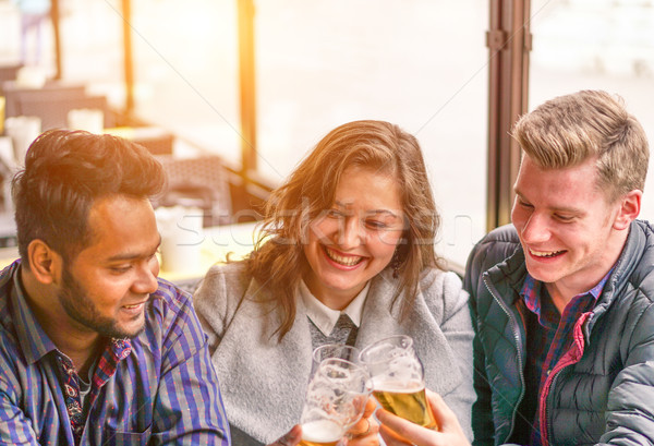 Multiracial best friends drinking a beer together sitting in bar Stock photo © DisobeyArt