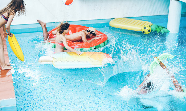 Happy friends jumping inside swimming pool  with tropical fruits Stock photo © DisobeyArt