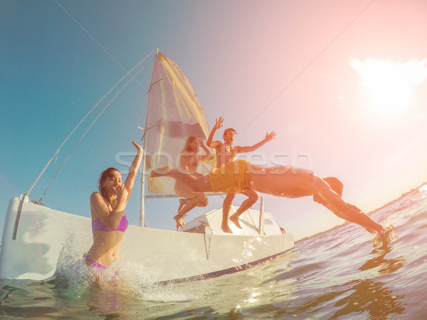 Happy friends diving from sailing boat into the sea - Young peop Stock photo © DisobeyArt