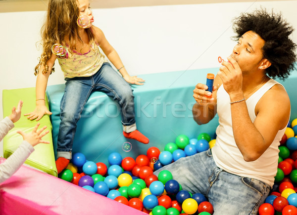 Young father playing with his daughter blowing soap bubbles insi Stock photo © DisobeyArt