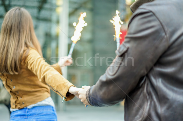 Young woman holding man with fireworks in hands during city fest Stock photo © DisobeyArt