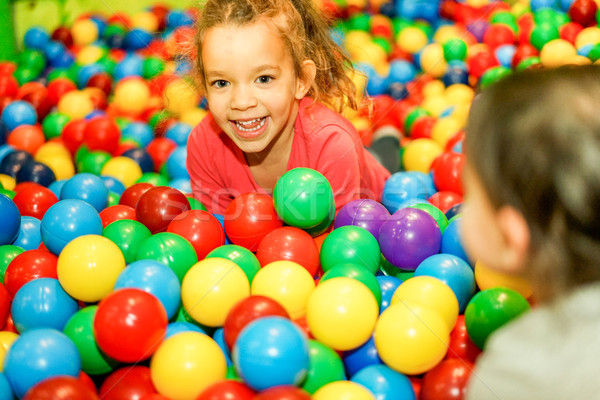 Cheerful children playing inside ball pit swimming pool - Happy  Stock photo © DisobeyArt
