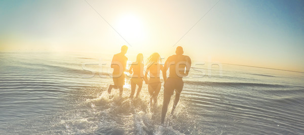 Young friends running into the sea at sunset - Freedom and trave Stock photo © DisobeyArt