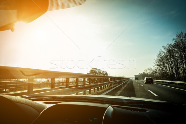 Car window view of trucks speeding in motorway with back sun lig Stock photo © DisobeyArt
