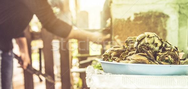 Young man cooking stuffed artichokes for barbecue dinner - Chef  Stock photo © DisobeyArt