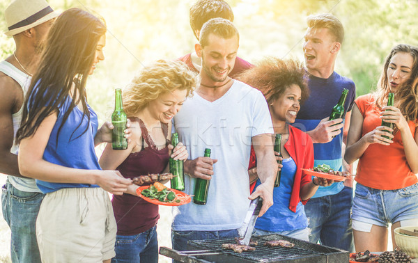 Happy young friends eating bbq meat and drinking beer outdoor in Stock photo © DisobeyArt