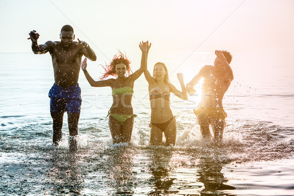 Happy diverse culture friends having fun inside water on the bea Stock photo © DisobeyArt
