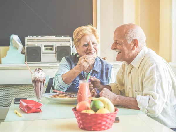 Happy senior couple having fun eating pancakes during united sta Stock photo © DisobeyArt