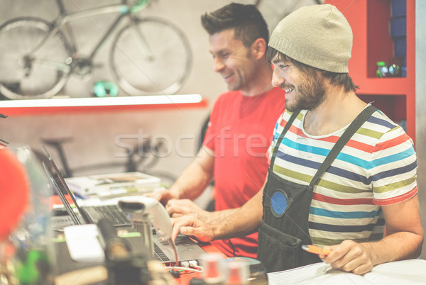 Two bicycle repairer colleagues working in bike garage - Positiv Stock photo © DisobeyArt