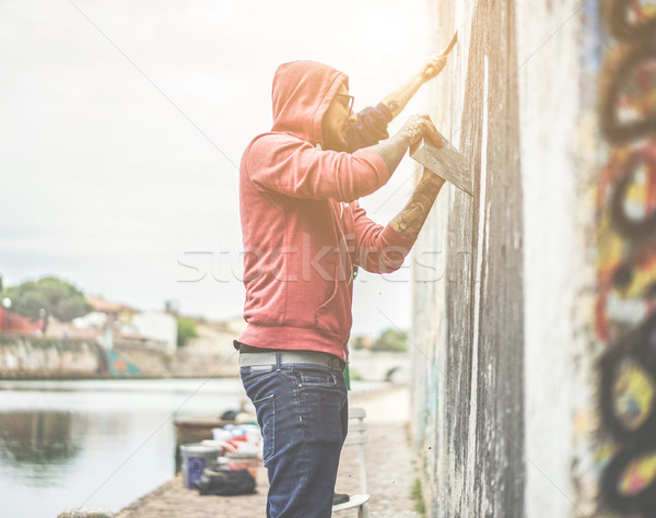 Two graffiti writers scraping the wall before painting their own Stock photo © DisobeyArt
