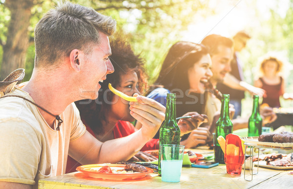 Happy friends doing barbecue on summer day in backyard home gard Stock photo © DisobeyArt