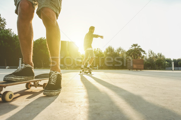 Two skaters friends training outdoor in city park at sunrise - Y Stock photo © DisobeyArt