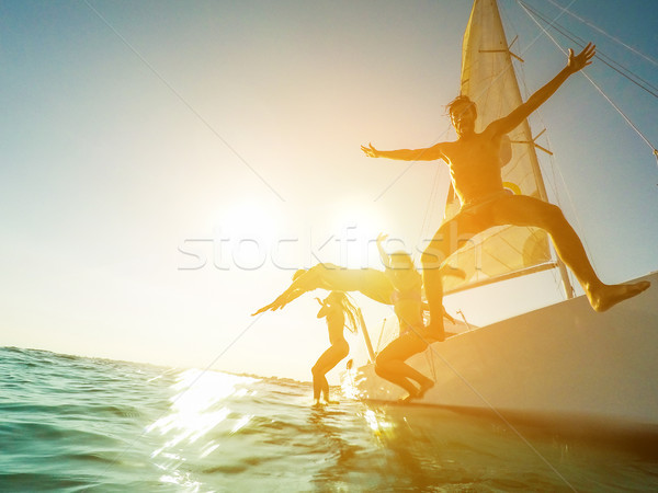 Crazy friends jumping off the boat into the ocean - Young happy  Stock photo © DisobeyArt