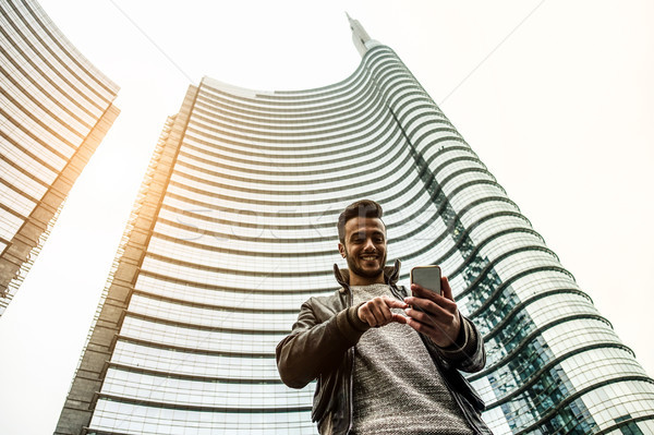 Happy bearded man using mobile cell phone in town finance center Stock photo © DisobeyArt