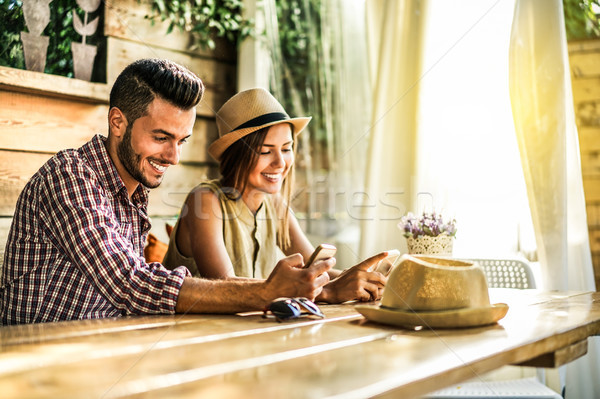 Young couple using mobile smartphones in bar cafe restaurant - T Stock photo © DisobeyArt