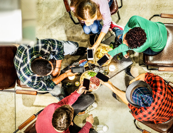 Top view of young friends using mobile smartphones in trendy pub Stock photo © DisobeyArt
