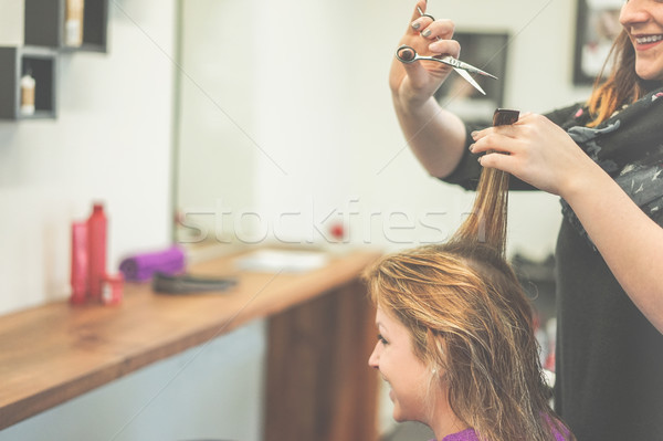 Cheerful hairdresser cutting woman hair for a new haircut style  Stock photo © DisobeyArt