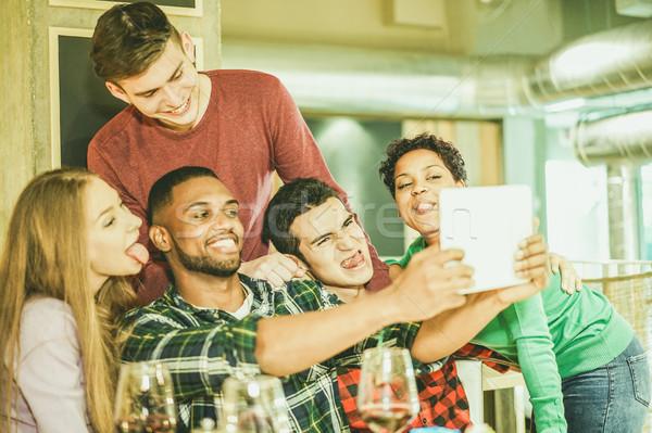 Groep vrolijk vrienden foto tablet Stockfoto © DisobeyArt