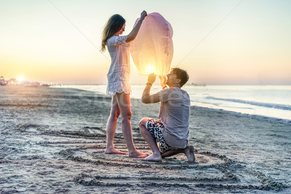 Young couple of lovers lighting sky lantern on the beach at suns Stock photo © DisobeyArt