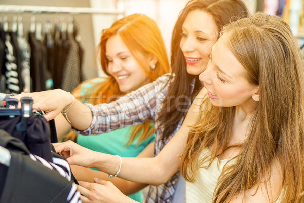 Young happy women doing shopping at the weekly cloth market - Ch Stock photo © DisobeyArt
