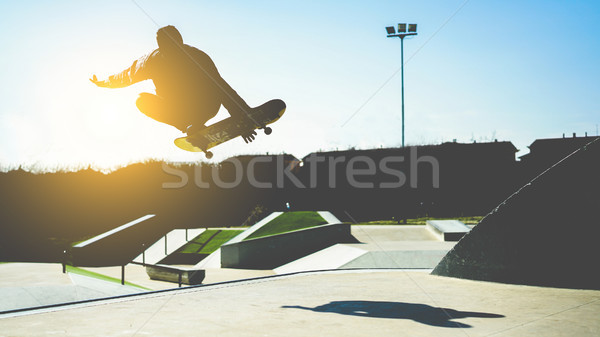 Silhouette of skater jumping on ramp at city park - Young man pe Stock photo © DisobeyArt