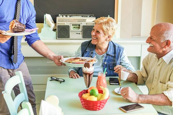 Happy senior couple doing breakfast with pancakes,muffin,smoothi Stock photo © DisobeyArt