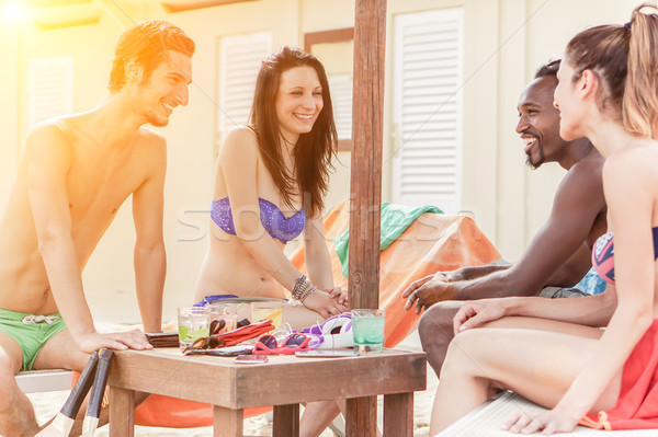 Multi ethnic friends enjoying a sunny day on the beach - Young p Stock photo © DisobeyArt