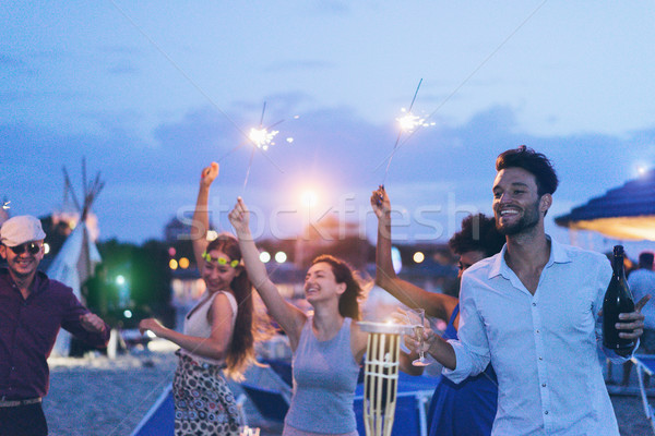 Happy friends making evening beach party outdoor with fireworks  Stock photo © DisobeyArt
