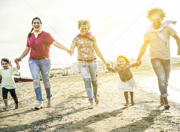 Mixed race family friends running and having fun on the beach -  Stock photo © DisobeyArt