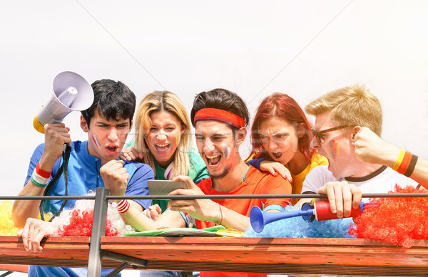 Young supporters from different countries watching sport on mobi Stock photo © DisobeyArt