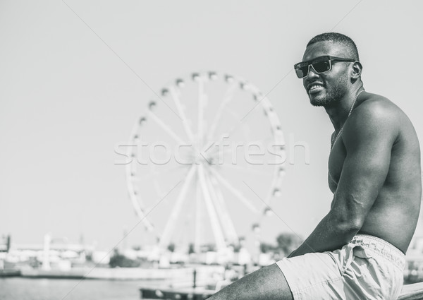 Young muscular black man sitting inside sailing boat with wonder Stock photo © DisobeyArt