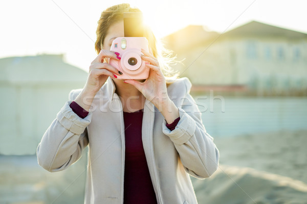 Young woman shooting with pink instant camera - Trendy girl taki Stock photo © DisobeyArt