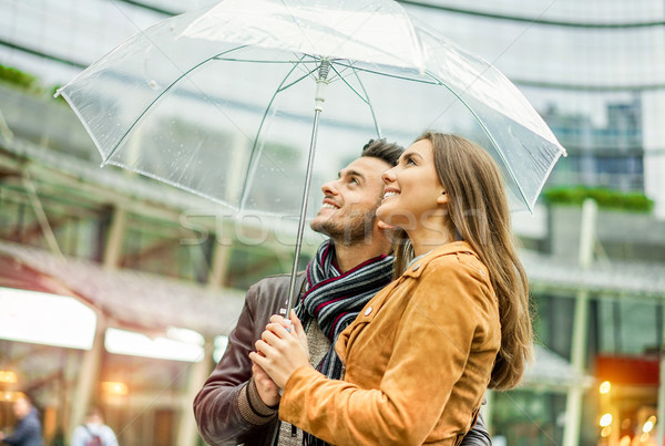 Young happy couple under soft raining day covering with transpar Stock photo © DisobeyArt