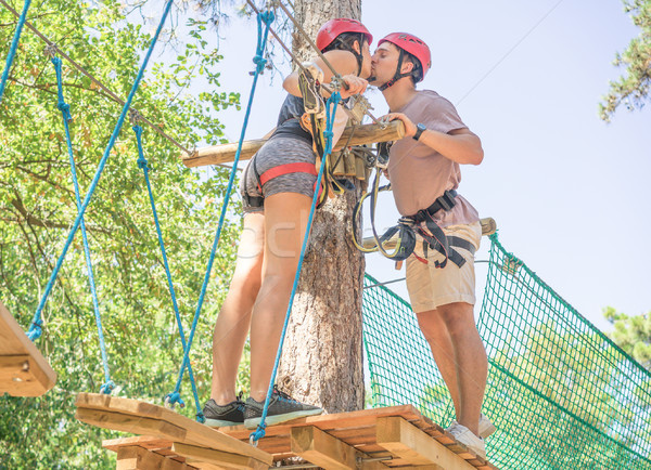 Couple of climbers kissing in adventure hiking park outdoor - Tr Stock photo © DisobeyArt