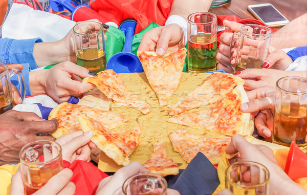 Multi ethnic hands of football friend supporter sharing pizza ma Stock photo © DisobeyArt
